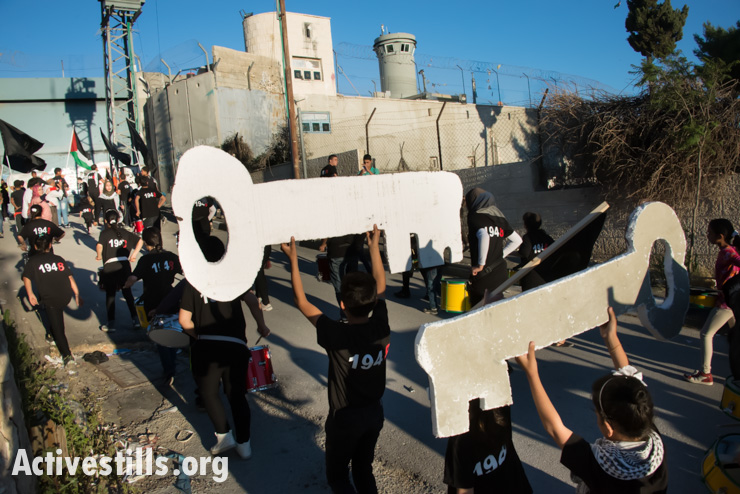 Children from Aida Refugee Camp carry keys symbolizing the right of return toward the Israeli separation wall during a Nakba commemoration event, Bethlehem, West Bank, May 14, 2014.