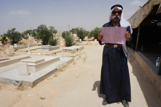 Sheikh Sayah A-Turi holds up an eviction notice in his village of Al-Arakib. (photo: Michal Rotem)