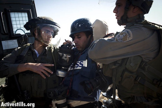 Israeli soldiers arrest a Palestinian journalist (photo: Activestills.org)