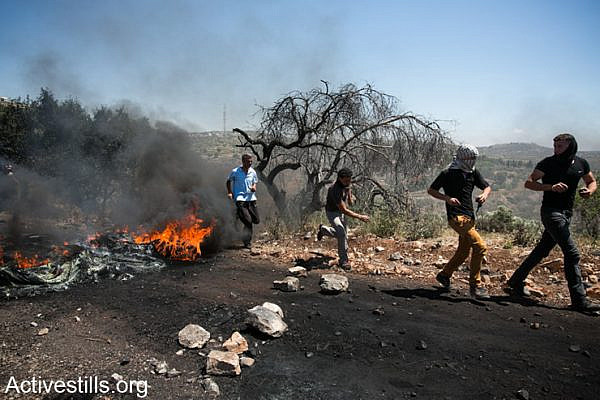 Demonstrators set fire during the weekly protest against the occupation in the West Bank village of Kafr Qaddum, May 2, 2014.