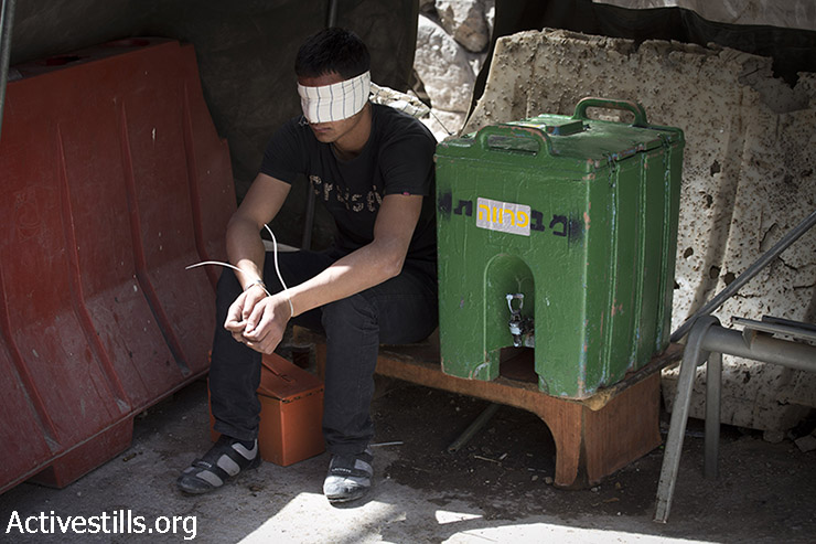 Palestinian youth sits blindfolded in a checkpoint after Israeli soldiers arrested him during clashes in the West Bank city of Hebron, June 16, 2014. (Oren Ziv/Activestills.org)
