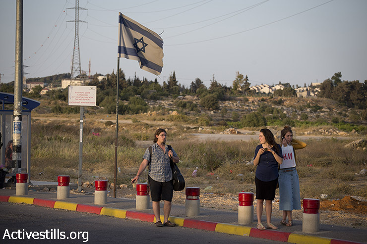 Israeli setters hitchhike at the Gush Etzion junction, next to the Palestinian town of Bethlehem, June 16, 2014. (Oren Ziv/Activestills.org)