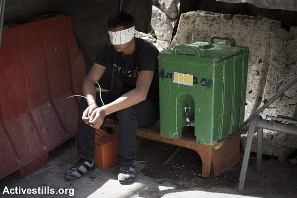 A Palestinian youth, arrested and blindfolded by Israeli soldiers during the closure on Hebron. (photo: Activestills)