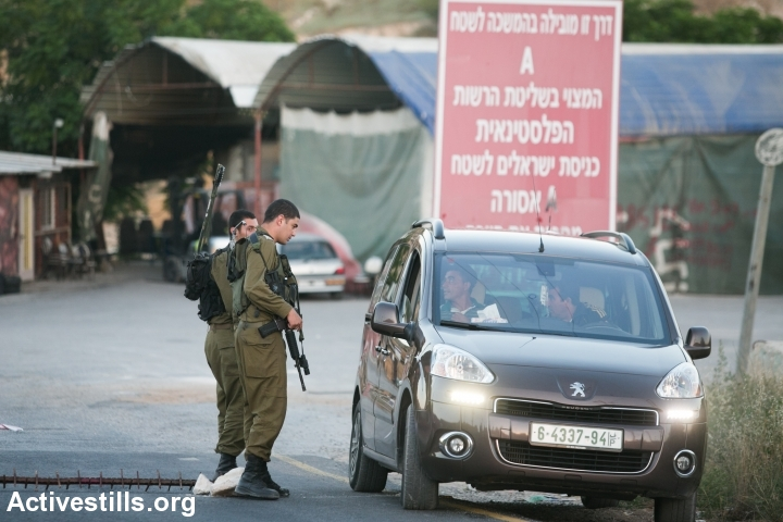 Israeli soldiers stop Palestinians at a flying check-point at the entrance to the West Bank city of Hebron, seen on June 15, 2014. A complete closure was put on the city after three Israeli teenagers went missing near a West Bank settlement. The three, all students at a Jewish seminary, went missing late on June 12 as they were hitchhiking between Bethlehem and Hebron and are believed to have been kidnapped. (Photo by Yotam Ronen/Activestills.org)