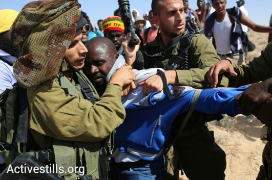 Israeli soldiers hold back an African asylum seeker during the march to the border with Egypt. (photo: Yotam Ronen/Activestills.org)
