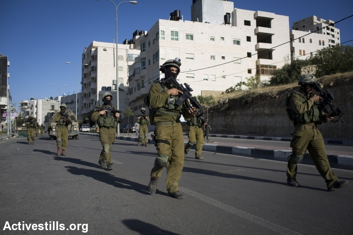 IDF soldiers march through the Palestinian-controlled areas of Hebron. (photo: Activestills)