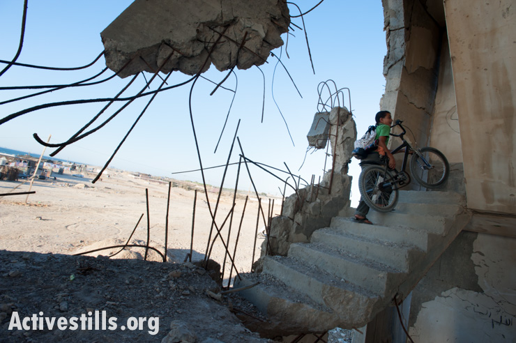 A Palestinian child plays among the ruins of buildings destroyed by Israeli air strikes during Operation Cast Lead in 2008-2009, July 4, 2012. (Activestills.0rg)