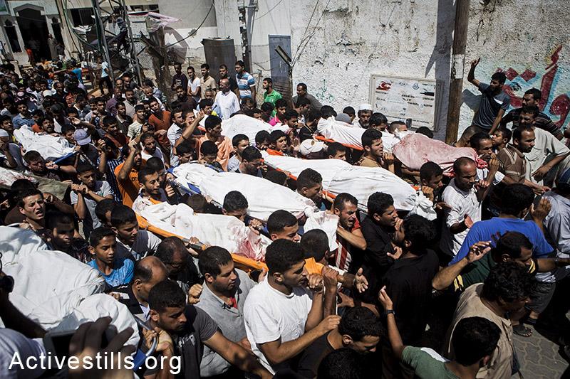 Funeral in Bani Suhaila for the 21 members of the Al-Najjar family, who were killed just before the ceasefire, east of Khan Younis, Gaza Strip, July 21, 2014.  The Al-Najjar family flew their homes in Khuza'a to take refuge fi-urther west.  Israeli attacks have killed 550 Palestinians in the current offensive, most of them civilians. Khuza'a has been under heavy attacks and many fled their village as the Israeli army physically occupies the village. Israeli attacks have killed more than 1,000 Palestinians and injured around 5,000 in the current offensive.