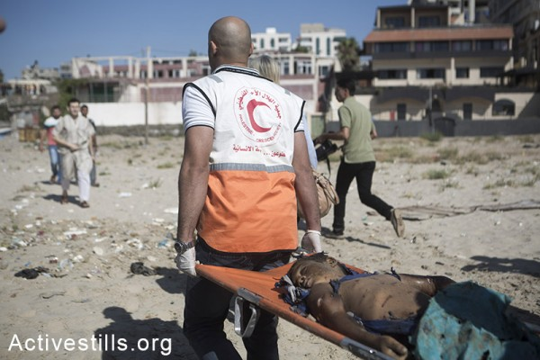 A Palestinian child, killed in an Israeli airstrike on Gaza beach, is carried away by paramedics, Gaza City, July 16, 2014. Four children were killed during the attack. (Anne Paq/Activestills.org)