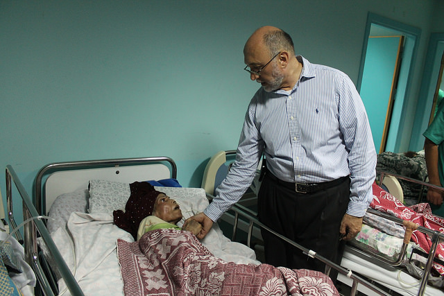 Dr. Basman Alashi, who directs El Wafa Medical Rehabilitation Hospital, comforts a patient during Israel's Operation Protective Edge. The facility, which had been targeted by repeated firing from nearby Israeli positions, was completely destroyed on July 23, 2014. (Joe Catron)
