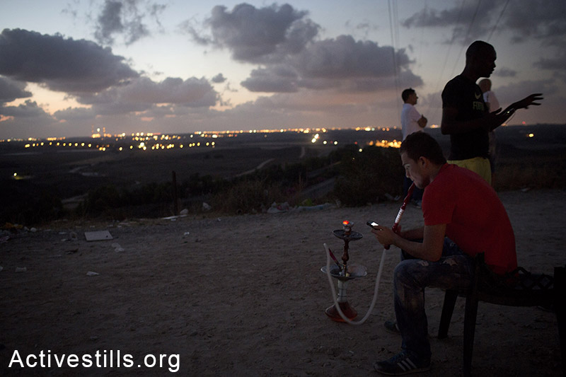 Israelis gather on a hill to watch  the Israeli army attacks on rhe Gaza strip, and rockets that are fired from Gaza to Israel, near the city of Sderot, July 15, 2014.