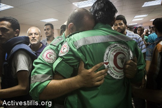 Medics at the Al-Shifa hospital mourn their colleague targeted and killed in Shejaiya neighbourhood earlier today, Gaza Strip, July 20, 104. Spokesman of the Palestinian ministry of health Ashraf al-Qidra said rescue teams evacuated more than 80 dead bodies from destroyed houses in Shejaiya including 17 children, 14 women and 4 elderly people. More than 200 injured people were taken to al-Shifa Hospital. Death toll in the Gaza Strip accedes 392 with over 2650 wounded since the beginning of the Israeli offensive. (Anne Paq/Activestills.org)
