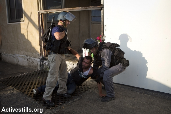 Israeli policemen arrest a Palestinian youth during clashes following a protest of Palestinians living in Israel against the Israeli attack on Gaza, in the northern city of Nazareth, July 21, 2014. Police used tear gas and a water canon to disperse the protest, arresting at least 10 youths. (photo: Activestills)