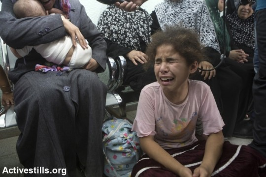 A Palestinian girl cries after an Israeli attack on Beit Hanoun elementary schools mourn in Kamal Edwan Hospital, Jabalyia, Gaza Strip, July 24. The school was being used as a shelter by 800 people. The attack killed at least 17 and injured more than 200 of the displaced civilians. Israeli attacks have killed 788 Palestinians and injured around 5,000 in the current offensive, most of them civilians. (photo: Anne Paq/Activestills)