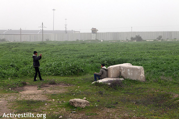 Palestinian children take pictures of each other in the no-go zone near Erez crossing, during the weekly demonstration against the occupation in Beit Hanoun, Gaza Strip, Tuesday, February 7, 2012. (Anne Paq/Activestills.org)