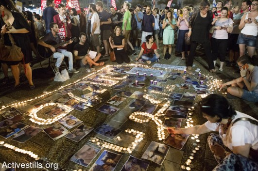 """Israeli activists light candles with the word """"sorry"""" in Arabic and Hebrew, during a protest against the attack on Gaza, Rabin Square, Tel Aviv, July 26, 2014. (Keren Manor/Activestills.org)"""