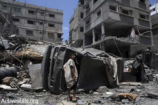 Homes in Beit Lahiya lie in ruins after the Israeli bombing of the Rozanah family home, Gaza Strip, August 2, 2014. The homes of five families were destroyed, leaving 60 people homeless. (Anne Paq/Activestills.org)