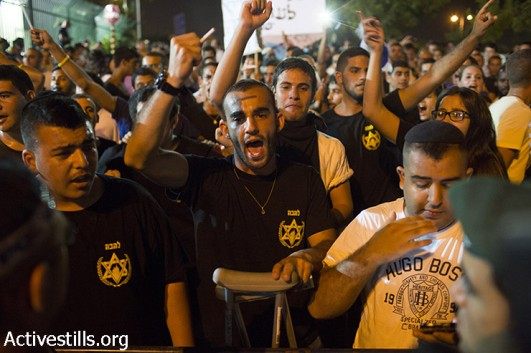 Right-wing Lehava activists shout slogans as they protest outside the wedding hall where Mahmoud Mansour, a Palestinian Israeli, and Morel Malcha, a Jewish Israeli, got married on August 17, 2014 in Rishon Letzion. Police arrested at least 7 right wing protesters, out of over 300 who were protesting against the wedding. (Oren Ziv/Activestills.org)