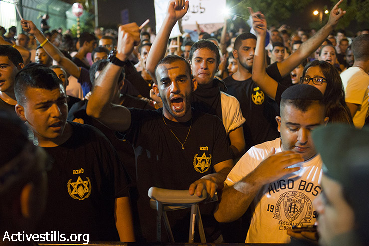 Right-wing supporters of the far-right Lehava group shout slogans as they protest outside the wedding hall where Mahmoud Mansour, an Arab-Israeli, and Morel Malcha, a Jewish, was married on August 17, 2014 in the Israeli costal city of Rishon Letzion. (Oren Ziv/Activestills.org)