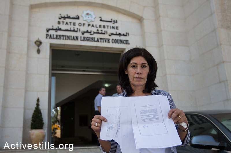 Khalida Jarrar, a member of the Palestinian Legislative Council, leader in the Popular Front for the Liberation of Palestine and longtime advocate for Palestinian political prisoners, showing an internal expulsion order given to her by Israeli soldiers who invaded her home in Ramallah at 1:30 am on August 20, 2014, ordering her leave Ramallah to Jericho within 24 hours. (Activestills.org)
