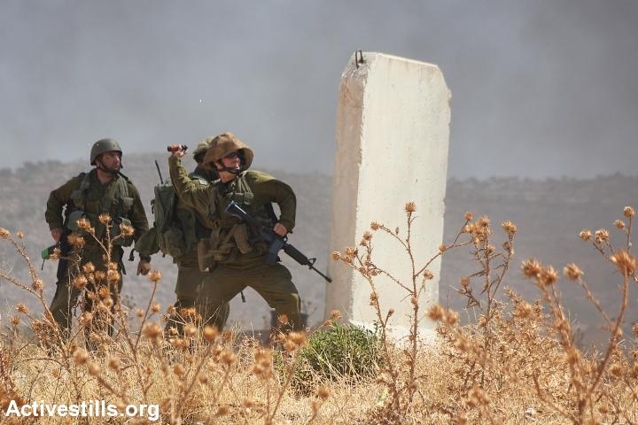 An Israeli soldier throws a stun grenade at Palestinian protesters in Beit Furik. (photo: Ahmad al-Bazz/Activestills.org)