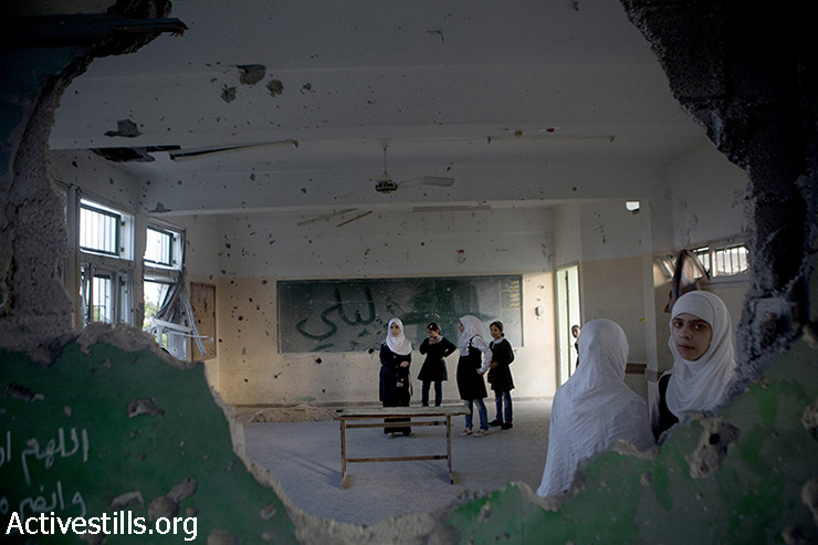 Palestinian school students stand in a destroyed classroom in the damaged Sobhi Abu Karsh Basic school in a destroyed quarter of the Shujayea neighborood, Gaza city, September 15, 2014. The school year has started with a three-week delay, due to the latest Israeli offensive during which 29 schools have been totally destroyed, and around 190 damaged. The first weeks are dedicated to recreational activities to help children to overcome the trauma due the the seven-week Israeli military offensive. 2,131 Palestinians were killed, including 501 children, and an estimated 18,000 housing units have been either destroyed or severely damaged, leaving more than 108,000 people homeless.