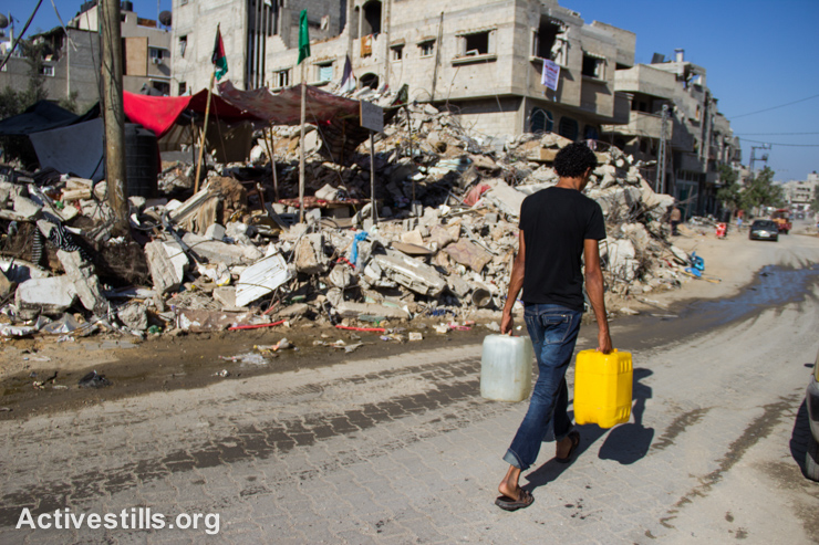 A Palestinian carries jugs of water through a destroyed section of the Shujayea neighborhood, east of Gaza city, September 4, 2014. (Activestills.org)