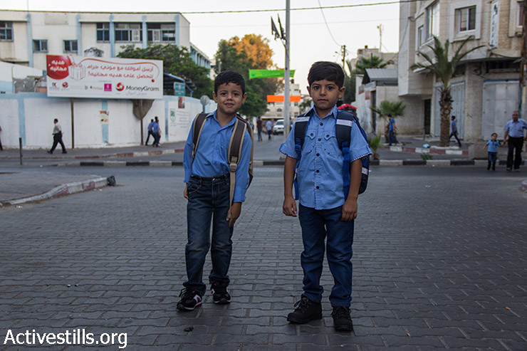 Boys walk to school on the first day of classes after Israeli attacks, Shujayea neighborhood, Gaza City, September 15, 2014. The school year has started with a three-week delay, due to the latest Israeli offensive during which 29 schools have been totally destroyed, and around 190 damaged. The first weeks are dedicated to recreational activities to help children to overcome the trauma due the the seven-week Israeli military offensive. 2,131 Palestinians were killed, including 501 children, and an estimated 18,000 housing units have been either destroyed or severely damaged, leaving more than 108,000 people homeless.