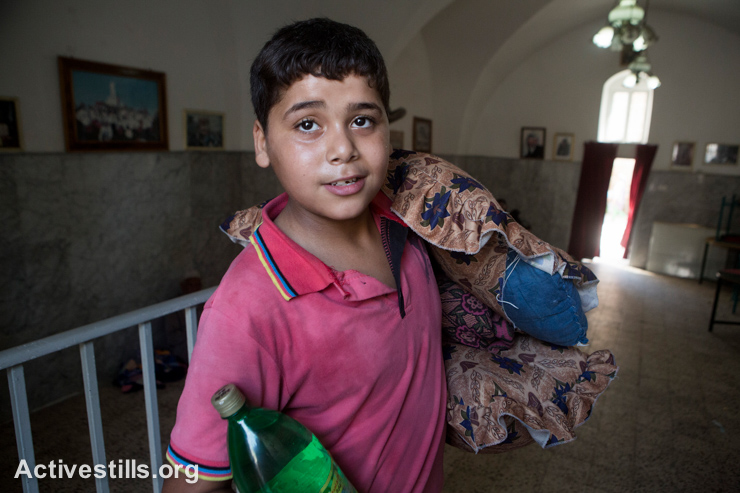 A Palestinian boy brings water and blankets inside the Greek Orthodox Church of St. Porphyrius in Gaza City where Palestinians have sought refuge. He was wounded in the head by an Israeli attack on the adjacent cemetery.