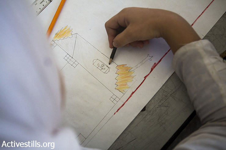 A Palestinian school student draws a home on fire during one of the activities conducted in the damaged Sobhi Abu Karsh school, Shujaiya neighborhood, Gaza City, September 15, 2014.