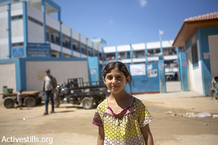 Wedhad, a Palestinian girl from Shujaiya, stands in front of the UNRWA school in the Al Zeitoun area of Gaza City, which is being used as temporary shelter for displaced Palestinians following the latest Israeli offensive, September 14, 2014. Wedhad said that she could not go to school as her school in Shujaiya was destroyed, and her mother is still looking for another school for her to register at.