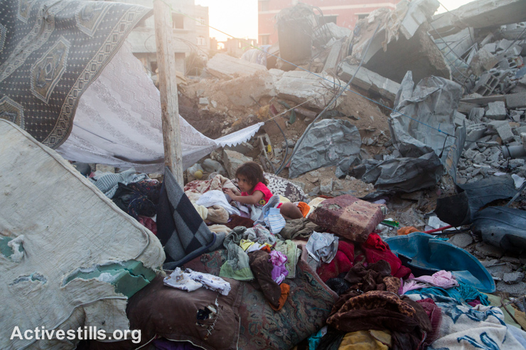 Ten days after the announcement of the long-term truce, a Palestinian child sits among clothing collected by his family in the rubble of their destroyed house in the At-Tuffah neighborhood of Gaza City, which was heavily attacked during the Israeli offensive.