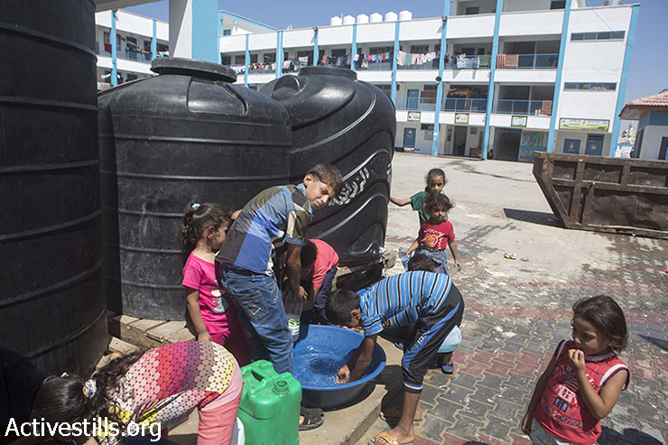 Palestinian children use water reservoirs to drink in an UNRWA school in zeitoun area which is used as temporary shelter for displaced Palestinians following the latest Israeli offensive , Gaza city, September 14, 2014. During the seven-week Israeli military offensive, 2,131 Palestinians were killed, including 501 children, and an estimated 18,000 housing units have been either destroyed or severely damaged, leaving more than 108,000 people homeless.