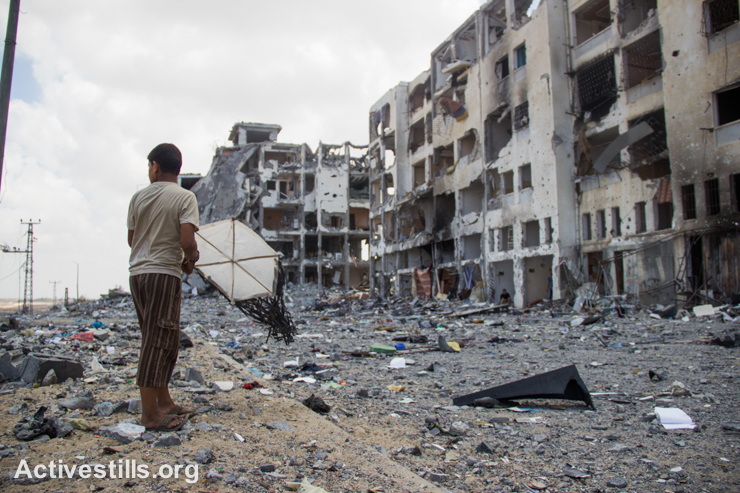 A Palestinian child with a kite stands in front of the destroyed Al Nada towers in Beit Hanoun, northern Gaza Strip. The towers had 90 flats.