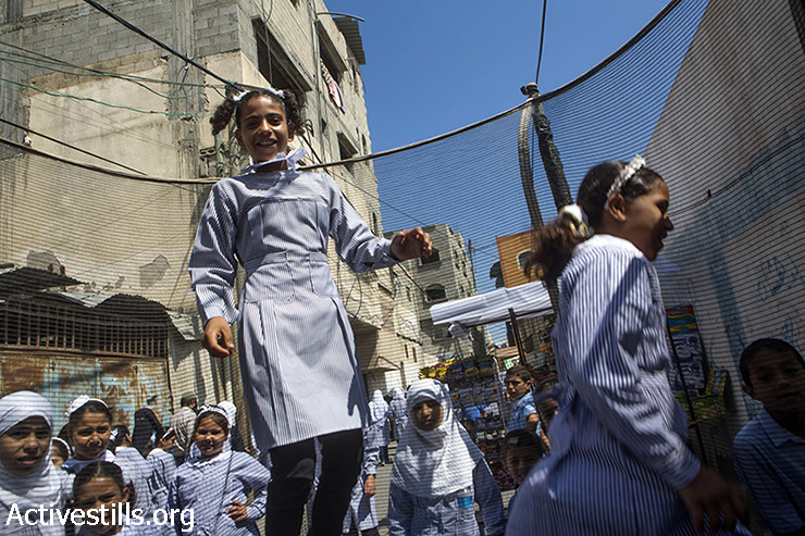 A Palestinian schoolgirl jumps on a trampoline after her first day of school, Gaza City, September 14, 2014.