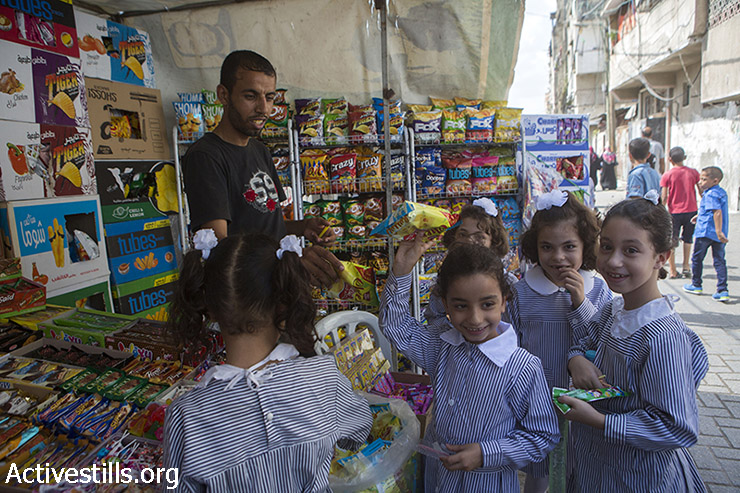 Palestinian school students buy snacks after their first day of school, Gaza city, September 14, 2014. The school year start with a three-week delay, due to the latest Israeli offensive during which 29 schools have been totally destroyed, and around 190 damaged. During the seven-week Israeli military offensive, 2,131 Palestinians were killed, including 501 children, and an estimated 18,000 housing units have been either destroyed or severely damaged, leaving more than 108,000 people homeless.