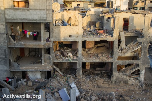A Palestinian woman stands near laundry hanging over a destroyed quarter of the Shujayea neighborood, Gaza City, September 4, 2014. (Activestills.org)