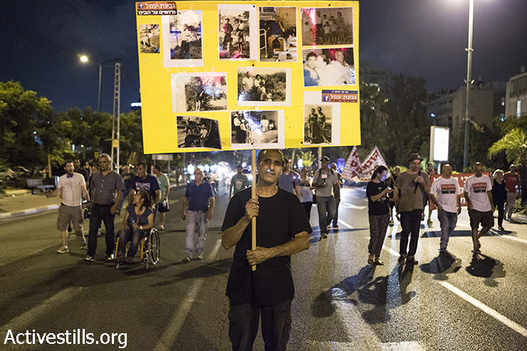 Demonstrator holds sign with photos of Givat Amal founders. (Keren Manor/Activestills)