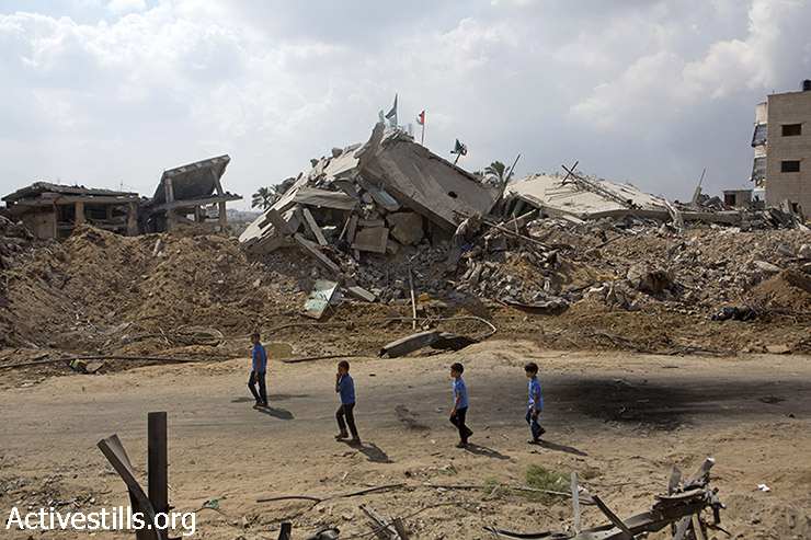 Palestinian students pass by destroyed buildings and homes in the Shujaiya neighborhood, Gaza City, September 15, 2014. Shujaiya was heavily attacked during the latest Israeli offensive, and some areas totally destroyed, leaving many Palestinians homeless.