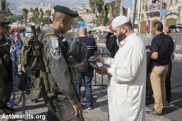 Israeli Border Police officers stand at the entrance to Jerusalem's Old City, as they prevent Muslim Palestinian worshippers from attending Friday prayers in Al Aqsa mosque, September 26, 2014. (Photo by Faiz Abu Rmeleh/Activestills.org)