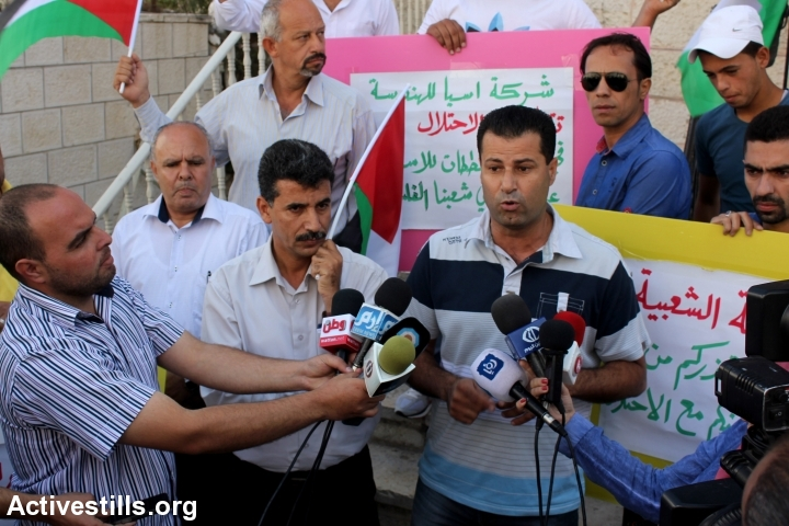 Palestinian activists protest in front of the office of Assia architectural company in Ramallah, West Bank, September 21, 2014. Activists discovered major cooperation between Assia company and the Israeli Civil Administration in connection with the 'E1' project east of Jerusalem. Last week, Israel announced that government plans to forcibly relocate 12,500 Palestinian Bedouin east of Jerusalem to a new town in the Jordan Valley were drafted without consulting the tribes. According to activists, Assia has agreed to take on the project. The new town, to be named Ramat Nu'eimeh, will be built in Area C, near Jericho in the Jordan Valley, and is slated to house about 12,500 people from Bedouin communities in the Jordan Valley and the Ma'ale Adumim area. (photo: Activestills)