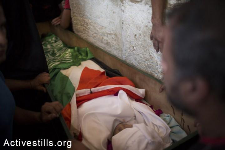 Muhammad Sunuqrut's body is prepared for the funeral procession, East Jerusalem, September 8, 2014. (Photo: Oren Ziv/Activestills.org)