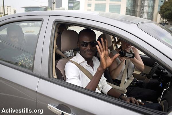 The author, Mutasim Ali, waves as he departs Tel Aviv for the Holot detention center on May 5, 2014. (Photo: Oren Ziv/Activestills.org)