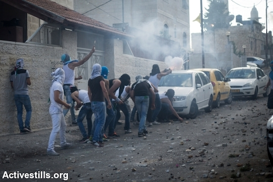 Palestinians throw stones at Israeli policemen during a protest following the death of a Palestinian teenager, in the East Jerusalem neighborhood of Wadi Joz, September 7, 2014. Mohammed Sunuqrut, 16, was wounded by police gunfire in the Wadi Joz neighborhood on August 31 and died from injuries on September 7. (Photo by Faiz Abu Rmeleh/Activestills.org)