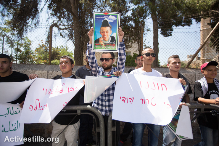 Palestinians hold placards during a demonstration outside the District Court in Jerusalem on September 3, 2014 during the trial of three Israeli suspects in the murder of Mohammed Abu Khader, who was kidnapped from East Jerusalem on July 2 and burned to death by Jewish extremists in a suspected revenge attack for the abduction and killing of three Israeli teenagers.