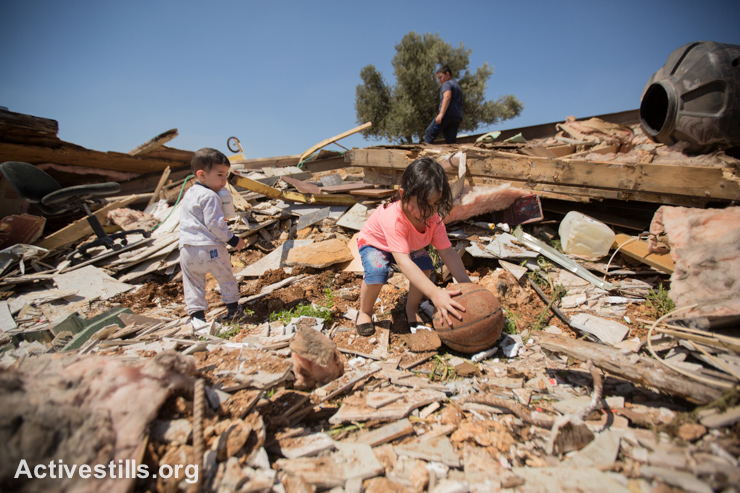 Palestinian children gather possessions among the rubble of their house that was demolished by the Jerusalem municipality in Beit Hanina in East Jerusalem, September 3, 2014.