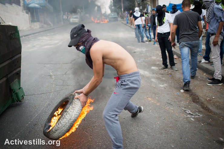A Palestinian youth holds a burning tire during a protest in the neighbourhood of Wadi Joz in East Jerusalem on September 8, 2014 following the death of Mohammed Sinokrot. Sinokrot, 16, was hit by police gunfire in the Wadi Joz neighbourhood on August 31 and died from injuries on September 7.