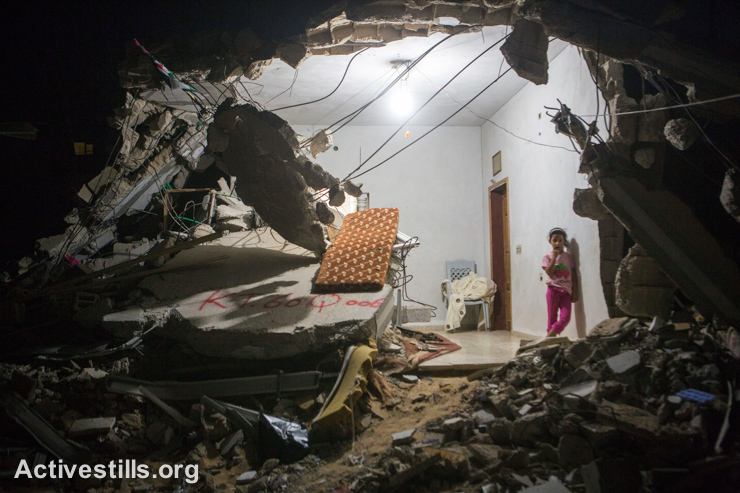 A Palestinian girl stands at night in her half-destroyed home in the village of Khuza'a, eastern Gaza Strip, September 9, 2014. Khuzaa'a was heavily attacked and damaged during the latest Israeli offensive. Parts of the village were occupied by Israeli soldiers and out of reach by the ambulances and the media during the fighting. As people were fleeing they were also attacked, and dozens were killed and many injured.