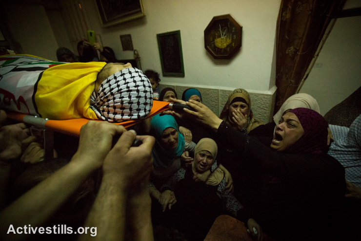 Palestinian women mourn as men carry the body of Eissa al-Qotri during his funeral at the Al-Ammari Refugee Camp near the West Bank city of Ramallah, September 10, 2014. Al-Qotri was killed by the Israeli army early on the same day during clashes between Palestinians and soldiers as the Israeli army raided the camp.