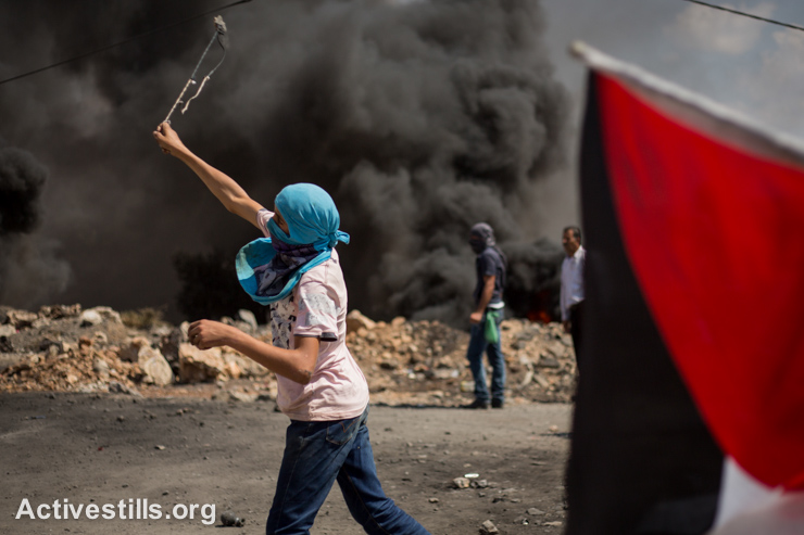 Youth throws stones during the weekly demonstration in Kafr Qaddum, a West Bank village located east of Qalqiliya, September 12, 2014. Locals began to organize demonstrations in July 2011 to protest the blocking of the main road linking Kafr Qaddum to Nablus.